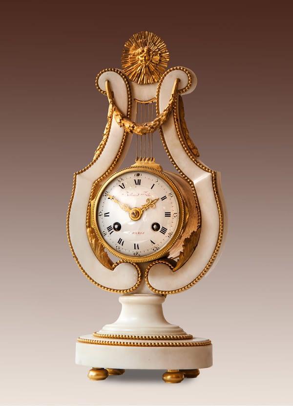 Lierpendule. Louis XVI-pendule in witmarmeren entourage in de vorm van een lier. Op de wijzerplaat gesigneerd Beliard Fils à Paris. ca. 1780.