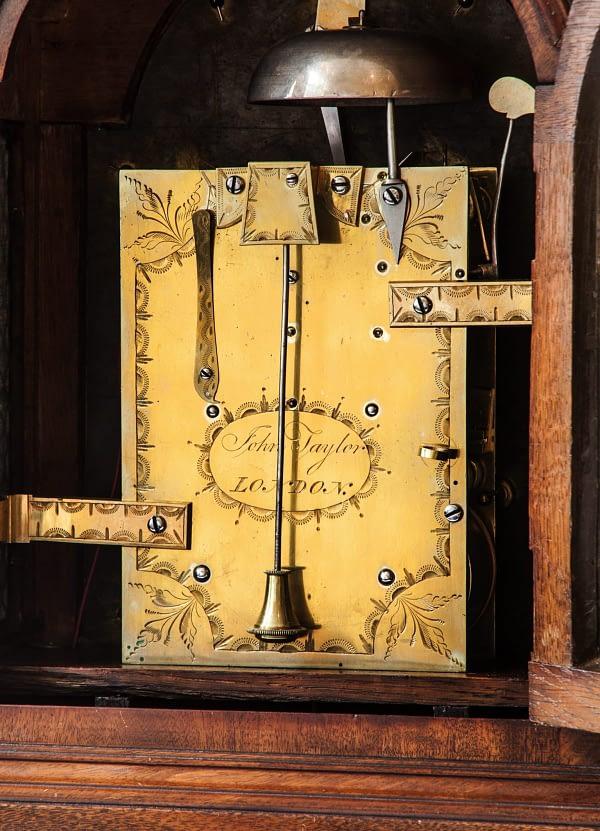 Bracketclock. Emaille wijzerplaat gesigneerd John Taylor, London. Datering circa 1800. Achterzijde gravure